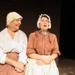 Photograph of Mrs Blaby and Mrs Peverill reminiscing outside in the sunshine in Lark Rise, Sewell Barn Theatre, Norwich