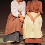 Photograph of Mrs Blaby (played by Marie Cooper actor) and Mrs Peverill (played by Ros Mace) talking about dresses