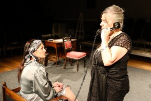 Photo of Maud taking a phone call as Anna Mary waits to hear where Marriette is onstage during Come into the Garden, Maud